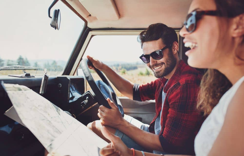 Couple on a road trip looking at map.